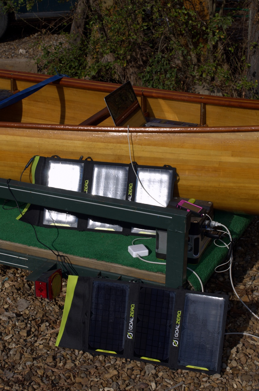 Solar panels and batteries soaking up the sun next to Cricket, our river ride.